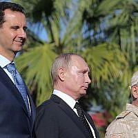 Le président syrien Bashar el-Assad, (à gauche), le président russe Vladimir Poutine et le ministre russe de la Défense Sergei Choigou inspectent un défilé militaire lors de leur visite à la base aérienne russe de Hmeimim, dans la province de Lattaquié, le 11 décembre 2017. (Crédit : Mikhail Klimentyev / AFP)