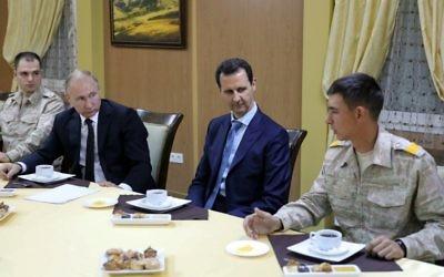 Le président russe Vladimir Poutine et son homologue syrien Bashar el-Assad, avec l'armée, dans la base militaire russe à Hmeimim, dans la province de Latka, le 11 décembre 2017. (Crédit : Mikhail KLIMENTYEV / POOL / AFP)