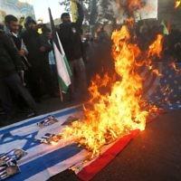 Des manifestants iraniens ont mis le feu aux drapeaux israéliens lors d'une manifestation dans la capitale de Téhéran, le 11 décembre 2017 pour dénoncer la déclaration de Jérusalem par le président américain Donald Trump comme capitale d'Israël. (Crédit : AFP / ATTA KENARE)