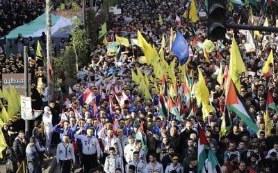 Des partisans du Hezbollah brandissent des drapeaux palestiniens et des drapeaux du Hezbollah durant une manifestation contre la reconnaissance de Jérusalem comme capitale d'Israël par Trump, à Beyrouth le 11 décembre 2017. (Crédit : AFP/Joseph EID)
