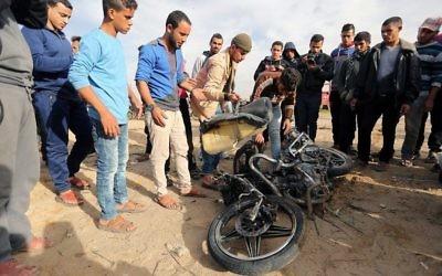Les Palestiniens inspectent les restes endommagés d'une motocyclette qui a explosé en tuant deux membres du Jihad islamique à Beit Lahia, dans le nord de la bande de Gaza, le 12 décembre 2017. (Crédit : AFP / MAHMUD HAMS)