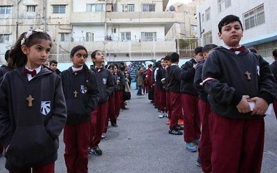 Des élèves chrétiens irakiens alignés dans la cour de l'école du Patriarcat latin dans le district de Marka dans la partie orientale de la capitale Amman, le 12 décembre 2017. (Crédit : AFP / Khalil Mazraawi)