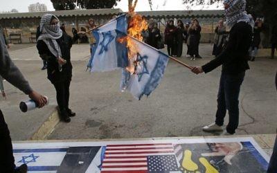 Des Palestiniens brûlent des drapeaux israéliens lors d'une manifestation à l'Université ouverte d'Al-Quds dans le village de Dura, à la périphérie de la ville de Hébron le 13 décembre 2017, alors que les protestations se poursuivent dans la région suite à la reconnaissance de Jérusalem comme capitale d'Israël par Donald Trump (PHOTO AFP / HAZEM BADER)