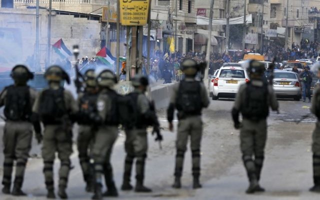 Les agents de police affrontent les émeutiers palestiniens durant des affrontements à proximité du poste de contrôle de Qalandiya en Cisjordanie, aux abords de Ramallah, le 15 décembre 2017 (Crédit : Abbas Momani/AFP)