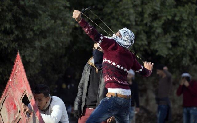 Un manifestant palestinien utilise une fronde pour jeter des pierres durant des affrontements avec les forces israéliennes de sécurité au checkpoint de Huwara, au sud de Naplouse, en Cisjordanie, le 15 décembre 2017 (Crédit :  AFP/Jaafar Ashtiyeh)