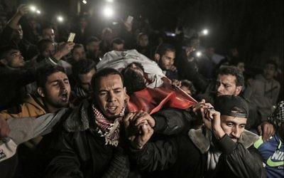 Les Palestiniens transportent le corps d'Ibrahim Abu Thurayeh à l'hôpital al-Shifa de Gaza, le 15 décembre 2017 (Crédit : AFP Photo/Mahmud Hams)