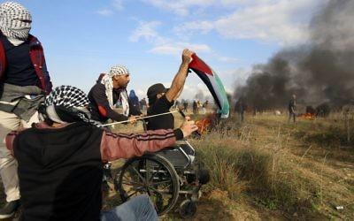 Le manifestant palestinien handicapé  Ibrahim Abu Thurayeh brandit un drapeau palestinien durant une manifestation le long de la frontière avec Gaza le 15 décembre 2017 dans des affrontements qui suivent la reconnaissance de Jérusalem comme capitale d'Israël du président américain Donald Trump (Crédit : MOHAMMED ABED / AFP)