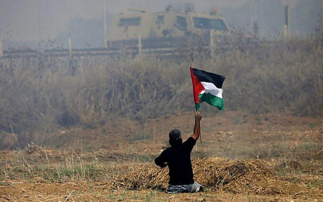 Le manifestant palestinien Ibrahim Abu Thurayeh brandit un drapeau palestinien lors d'affrontements avec des soldats israéliens près de la barrière frontalière à l'est de la ville de Gaza, le 19 mai 2017. (Crédit : AFP / MOHAMMED ABED / Archives)