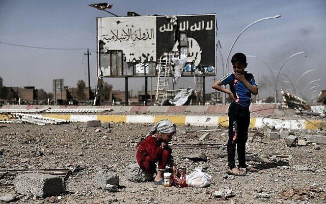 Cette photo prise le 12 mars 2017 montre des enfants irakiens assis dans les décombres d'une rue du quartier de Naplouse à Mossoul devant un tableau portant le logo de l'Etat islamique durant une offensive des forces de sécurité pour la reprise des quartiers ouest de la ville, aux mains de l'EI (Crédit : AFP PHOTO / ARIS MESSINIS)