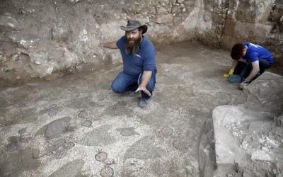 Benyamin Storchan, directeur des fouilles pour l'Autorité israélienne des antiquités, montre un sol décoré, vestige d'un monastère de l'ère byzantine, à Beit Shemesh, le 20 décembre 2017. (Crédit : AFP / MENAHEM KAHANA