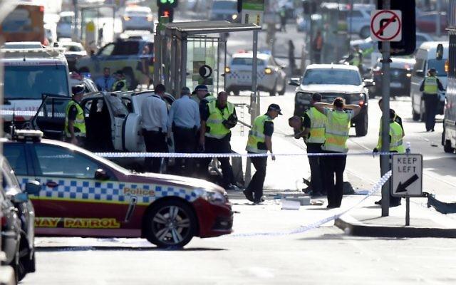La police et les secouristes sur les lieux où une voiture a percuté délibérément des piétons dans la rue Flinders à Melbourne le 21 décembre 2017 (crédit : AFP PHOTO / Mal Fairclough)