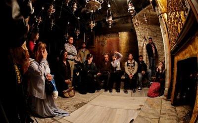 Les fidèles chrétiens prient près de l'étoile d'argent à 14 branches dans la Grotte, considérée comme l'endroit exact où Jésus Christ est né, dans l'église de la Nativité à Bethléem en Cisjordanie, le 21 décembre 2017 (Crédit : AFP PHOTO / THOMAS COEX)