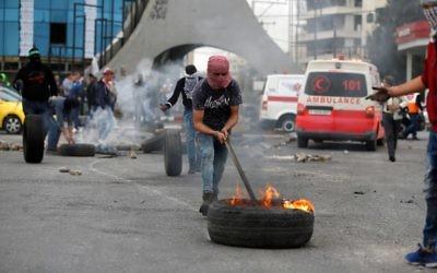 Des manifestants palestiniens brûlent des pneus durant une manifestation au nord de Ramallah, le 22 décembre 2017. (Crédit : AFP/Abbas MOMANI)