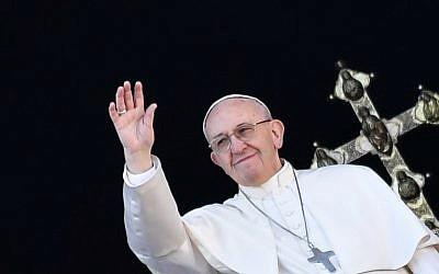 """Le pape François salue les fidèles depuis le balcon de la Basilique au Vatican après son traditionnel message """"Urbi et Orbi"""" le 25 décembre 2017. (Crédit : AFP / Andreas SOLARO)"""