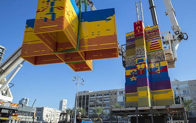 Des ouvriers et des bénévoles aident à assembler des briques de LEGO sur la place Rabin, à Tel Aviv, le 27 décembre 2017, alors que a ville tente de battre un record. (Crédit : AFP / JACK GUEZ)
