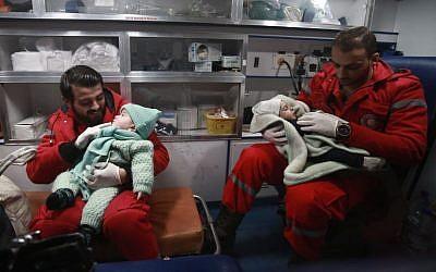 Des ambulanciers syriens distraient des enfants dans une ambulance, pendant la deuxième nuit de l'opération d'évacuation coordonnée par le Croissant rouge syrien et le CICR, à Douma, dans la région de la Ghouta orientale, le 27 décembre 2017. (Crédit : AFP/ABDULMONAM EASSA)