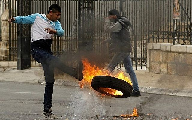 Un manifestant palestinien donne un coup de pied à un pneu en feu durant des affrontements avec les forces israéliennes après les prières du vendredi à Bethléem, en Cisjordanie, le 29 décembre 2017  (Crédit : AFP / Musa al Shaer)