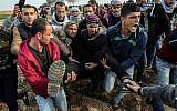 Des manifestants palestiniens transportent un blessé durant un affrontement contre les forces israéliennes près de la frontière entre Israël et Gaza dans la ville de Khan Yunis, dans le sud de Gaza, le 29 décembre 2017 (Crédit :  AFP PHOTO / SAID KHATIB)