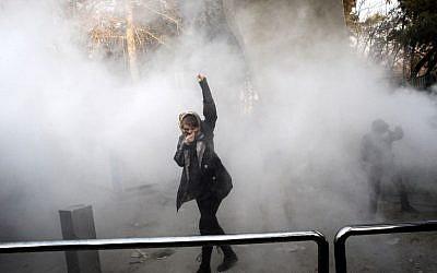 Une Iranienne lève le poing dans la fumée des gaz lacrymogènes à l'université de Téhéran durant une manifestation contre les problèmes économiques dans la capitale iranienne, le 30 décembre 2017 (Crédit : AFP PHOTO / STR)