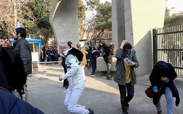 Des étudiants iraniens fuient les gaz lacrymogènes à l'université de Téhéran durant une manifestation, le 30 décembre 2017 (Crédit : AFP PHOTO / STR)