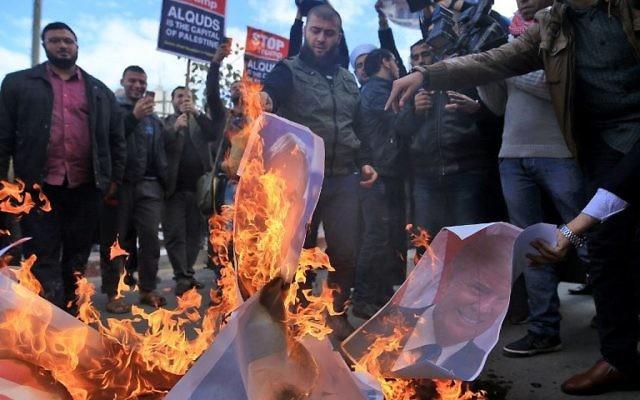 Des manifestants palestiniens brûlent des photos du président américain Donald Trump et du Premier ministre Benjamin Netanyahu après la décision de Trump de reconnaître Jérusalem comme capitale d'Israël, dans la ville de Gaza, le 7 décembre 2017 (AFP PHOTO / MOHAMMED ABED)