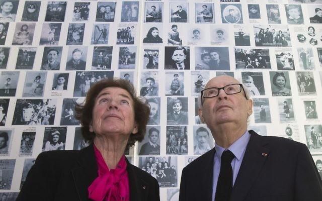 Serge Klarsfeld et sa femme Beate, les Français «chasseurs de nazis», regardent des photos de jeunes juifs déportés de France, au Mémorial de la Shoah à Paris, le 5 décembre 2017. (Crédit : AP / Michel Euler)