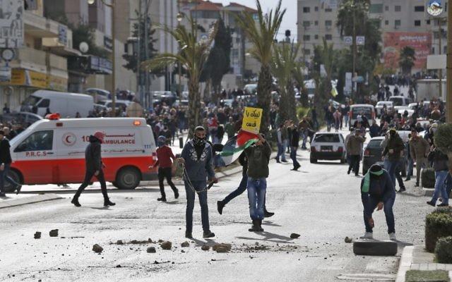 Des manifestants palestiniens lors d'affrontements avec les forces israéliennes près d'un poste de contrôle dans la ville de Ramallah, en Cisjordanie, le 7 décembre 2017 (ABBAS MOMANI / AFP)
