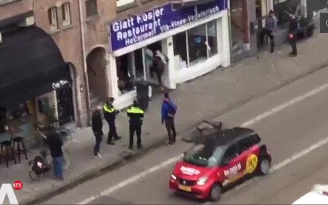 Un homme portant keffieh et drapeau palestiniens brise la vitrine d'un restaurant casher à Amsterdam, le 7 décembre 2017 (Crédit : capture d'écran Télévision néerlandaise AT5)