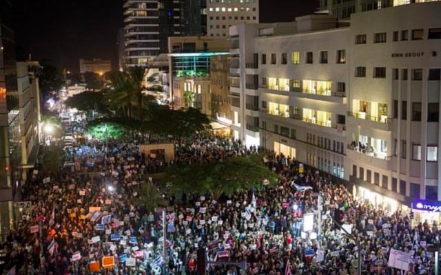 Des Israéliens brandissent des pancartes et scandent des slogans lors d'une manifestation contre la corruption, à Tel Aviv le 23 décembre 2017. (Crédit : Miriam Alster / Flash90)