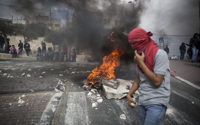 Un jeune palestinien tient des pierres à la main durant un affrontement avec la police israélienne dans le quartier de Sur Baher, à Jérusalem-est, le 7 octobre 2015 (Crédit : Hadas Parush/Flash90)