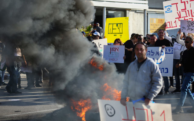 Les employés de l'entreprise Teva protestent contre le plan de licenciement de l'entreprise de centaines d'employés, aux abords du bâtiment de TEVA Pharmaceutical Industries à Ashdod, le 17 décembre 2017 (Crédit : Flash90)