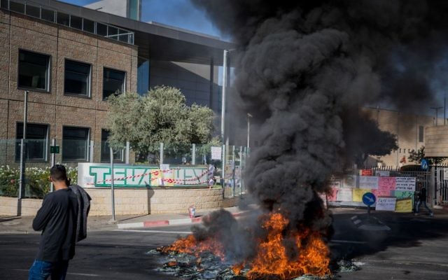Les employés de Teva brûlent des pneus dans une manifestation contre le licenciement de centaines d'employés par la compagnie aux abords du bâtiment de TEVA à Jérusalem, le 17 décembre 2017 (Crédit : Noam Revkin Fenton/Flash90)
