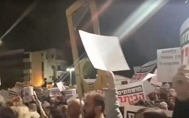 Un homme brandissant une fausse guillotine en carton assiste à un rassemblement anti-Netanyahu à Tel Aviv le 23 décembre 2017 (Crédit : capture d'écran 0404.co.il)
