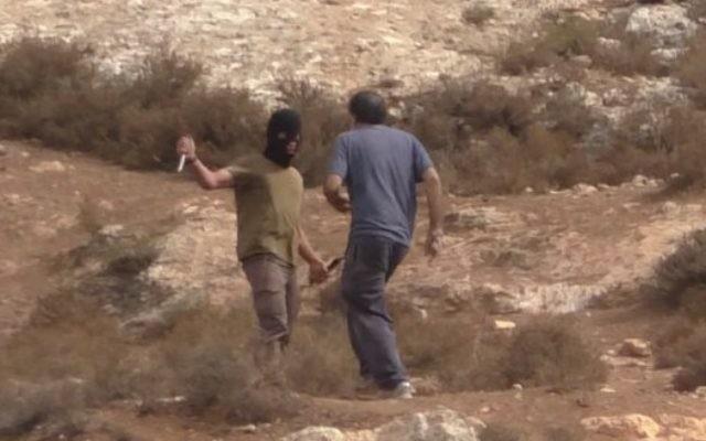 Un extrémiste de droite masqué attaque Arik Ascherman, chef de l'ONG Rabbis for Human Rights. (Crédit : capture d'écran Youtube)