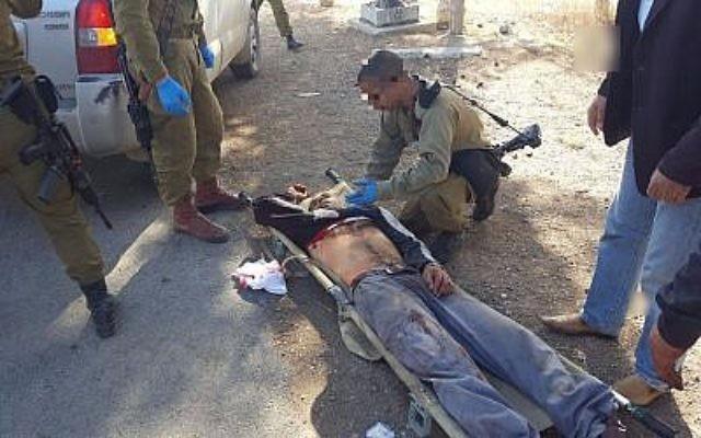Des soldats de l'armée israélienne s'occupent de Mahmoud Zaal Odeh après qu'il a été blessé par un habitant d'implantation israélien aux abords du village de Qusra le 30 novembre 2017 (Autorisation)