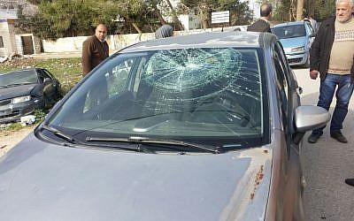 Les résidents Palestiniens de Burin devant une voiture au pare-brise fracassé par des résidents d'implantations israéliens qui ont attaqué le village, 28 décembre 2017. (Crédit : Yesh Din)