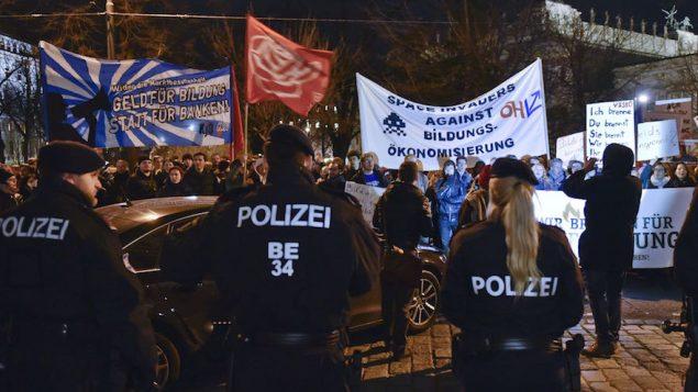 Des manifestants brandissent des bannières et des panneaux durant une manifestation contre la coalition passée entre le parti populaire autrichien (OVP) et le parti de la Liberté de droite (FPO) le 14 décembre 2017 aux abords du parlement de Vienne. (Crédit : AFP PHOTO / APA / HERBERT NEUBAUER)