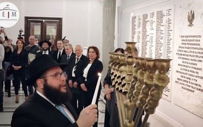 Chabad Rabbi Shalom Dov Ber Stambler lights the hannukah candles in Polish Parliament on December 12, 2017. (Screen capture/Facebook)
