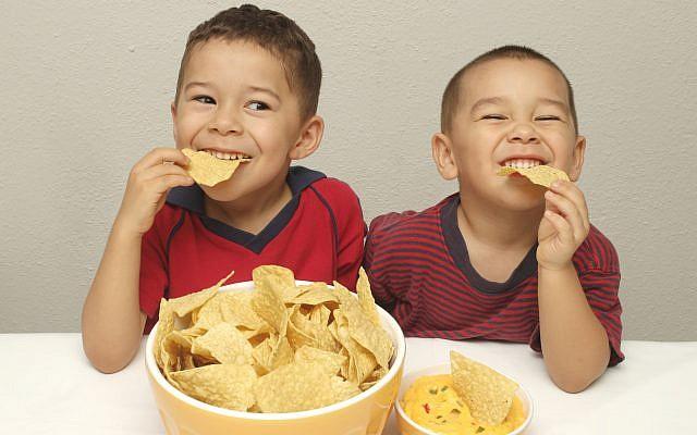 Illustration : deux enfants espagnols mangent des chips. (Crédit : (Hugh Stonelan via Stock/Getty Images)