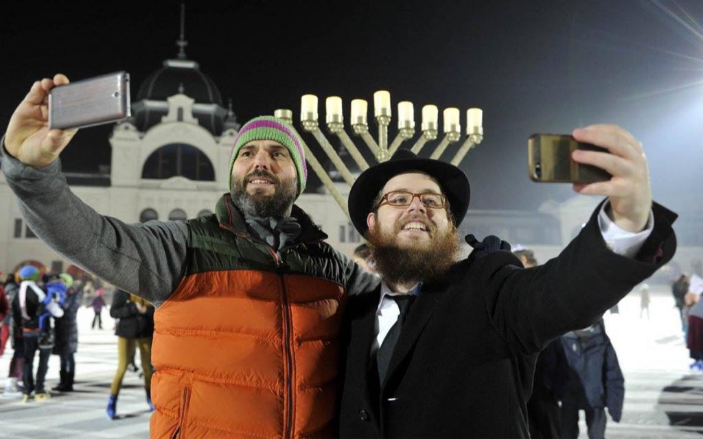 Le rabbin Slomo Koves, à droite, et un participant au Hanoukka loubavitch hongrois sur glace de 2015, prennent des selfies à la patinoire City Park de Budapest, le 6 décembre 2015. (Courtoisie d'EMIH / via JTA)