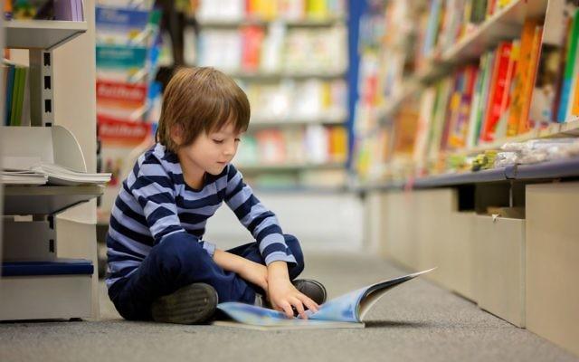 Photo d'illustration d'un petit garçon assis dans une librairie en train de lire (Crédit : tatyana_tomsickova/ IStock by Getty Images)