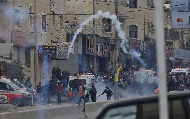 Des manifestants palestiniens affrontent les forces de l'ordre israéliennes près du checkpoint de Qalandiya, en Cisjordanie, le 20 décembre 2017, après la reconnaissance de Jérusalem comme capitale d'Israël par Donald Trump. (Crédit : AFP / ABBAS MOMANI)