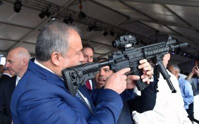 Le ministre de la Défense Avigdor Liberman inspecte le viseur d'un fusil dans une usine d'armement à Sderot, le 14 décembre 2017. (Crédit : Ariel Hermoni/Defense Ministry)