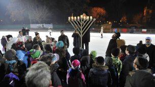 Le Rabbin Slomo Koves allumant une Menorah lors de l'événement Hanoukka loubavitch sur glace de Hongrie en 2015, à la patinoire City Park de Budapest, le 6 décembre 2015. (Courtoisie de EMIH / via JTA)