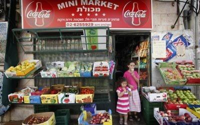 Deux fillettes mangent une glace en sortant d'un petit commerce de Jérusalem, le 2 août 2010 (Crédit : Miriam Alster/Flash90)