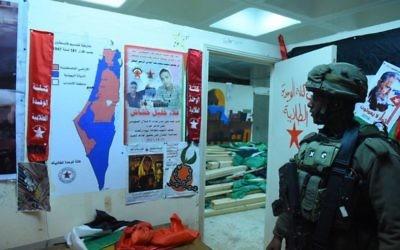 Un soldat de Tsahal se tient à côté de ce que l'armée a appelé des « matériaux d'incitation à la terreur » qui ont été saisis lors de raids nocturnes, le 14 décembre 2017 (Crédit : Armée israélienne)
