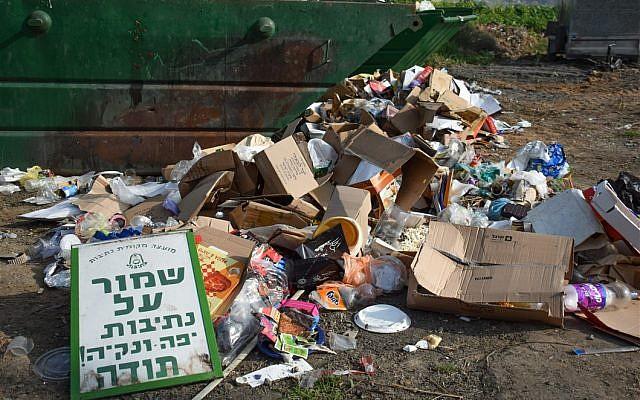 Un tas d'ordures sous un panneau qui demande aux gens de s'abstenir de jeter des déchets (Crédit : Autorisation Yael Argov)