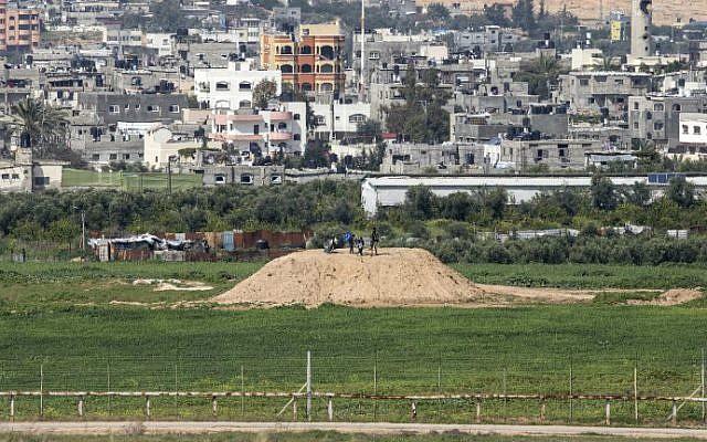 Une photo prise depuis le côté israélien de la frontière avec Gaza montre un Palestinien et des enfants au sommet d'un avant-poste du Hamas le long de la frontière, le 25 février 2016 (Jack Guez / AFP)