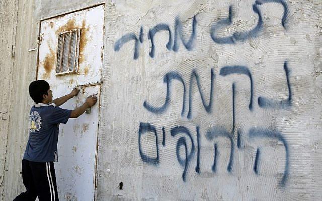 Un Palestinien ouvre une porte après que des graffitis hébreux aient été tagués sur un mur, prétendument par des colons juifs, dans le village d'Aqraba, en Cisjordanie, près de la ville de Naplouse, le 2 juillet 2014 (AFP / JAAFAR ASHTIYEH)