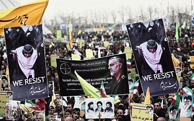 Des manifestants iraniens tiennent un portrait du général de division Qassem Soleimani, commandant des forces al-Quds des gardiens de la révolution iranienne et une personnalité centrale dans la propagation violente de la révolution iranienne. Photo prise place Azadi à Téhéran le 11 février 2015 (Crédit : Behrouz Mehri/AFP)